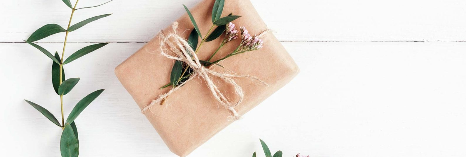 a wrapped gift in brown craft paper and fresh flowers