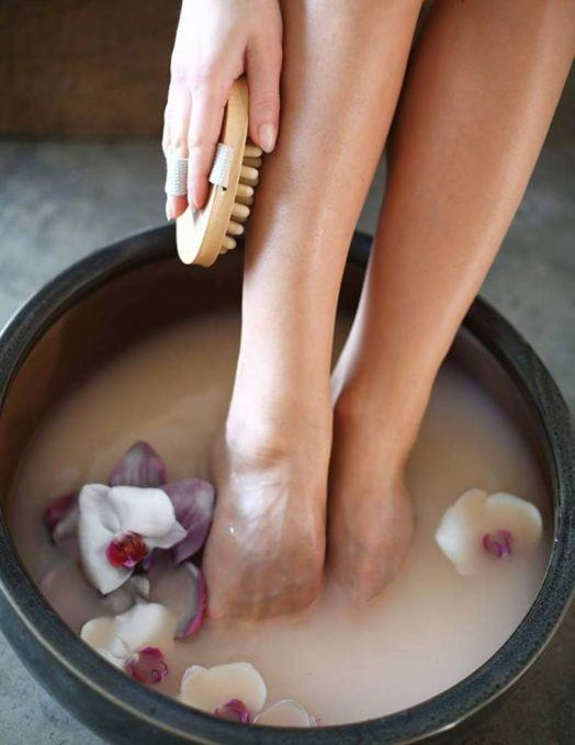 Woman exfoliating legs with brush in petal filled foot bath
