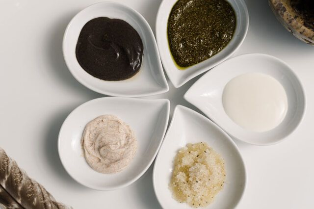 five small plates with different scrubs